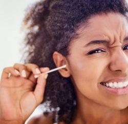 Jeune femme qui se lave les oreilles avec un coton-tige