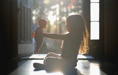 Petite fille assise par terre qui joue à la poupée