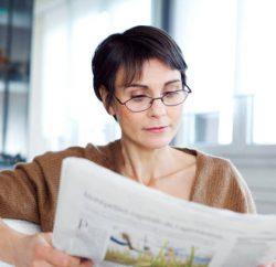 Femme presbyte qui lit son journal avec des lunettes de lecture