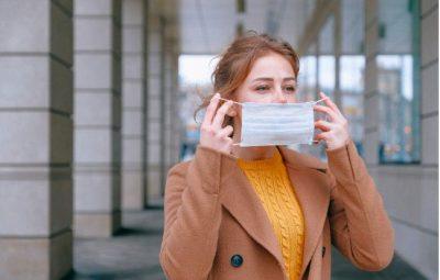 Jeune femme qui enfile un masque pour faire barrière contre les microbes
